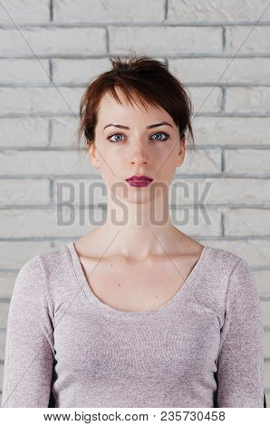 A Caucasian Pretty Girl With Neutral Face Expression, Big Blue Eyes, Full Pink Lips, With White Bric