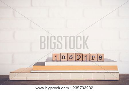The Word Inspire, Alphabet On Wooden Cubes On Top Of Books. Background Copy Space, Vintage And Minim