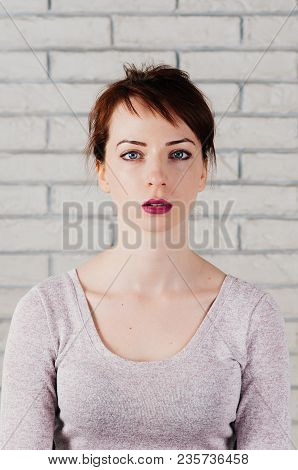 A Pretty Girl With Surprised Face, Big Blue Eyes, Brows Up, With White Brick Wall In The Background.