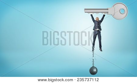 A Small Businessman Holds Up A Huge Metal Key While Getting Free From A Broken Ball And Chain. Free