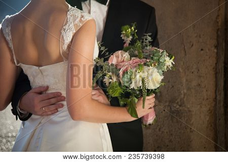 Newlyweds Hug And Hold Pink, White Wedding Flowers, Bride Is Dressed In Classic Lace White Wedding D