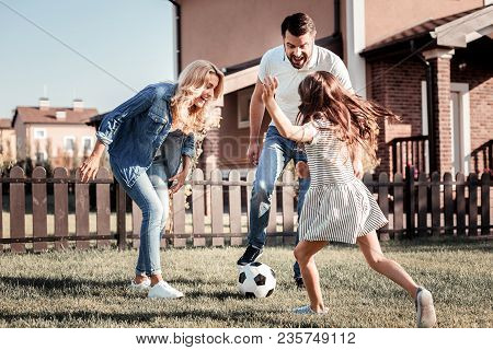 Play Together. Friendly Lovely Happy Family Having Fun Laughing And Playing Football Together On The