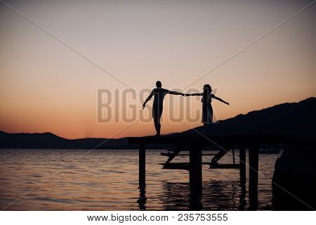 Couple In Love On Romantic Date In Evening At Dock, Copy Space. Romance And Love Concept. Silhouette