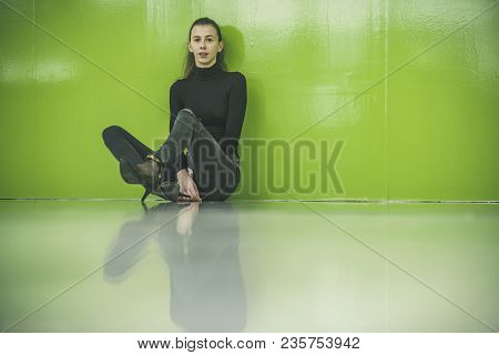 Sexy Girl Wearing High Heels Sitting On Floor. Woman In Black Clothes Near Green Wall. Girl With Ser