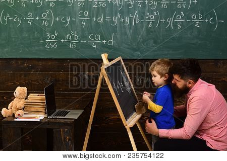 Pupil With Teacher At School. Side View Father And Son Learn Arithmetic. Daddy Explaining Equation T
