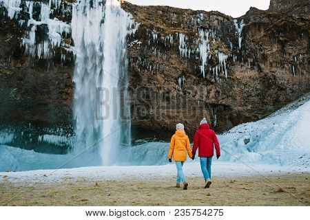 Man In Red Jacket And Woman In Yellow Jacket Walking Together Next To Waterfall. Iceland Travelers.