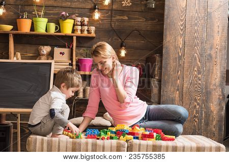 Mother And Son Play With Constructor. Childhood Concept. Nursery With Chalkboard On Background. Fami
