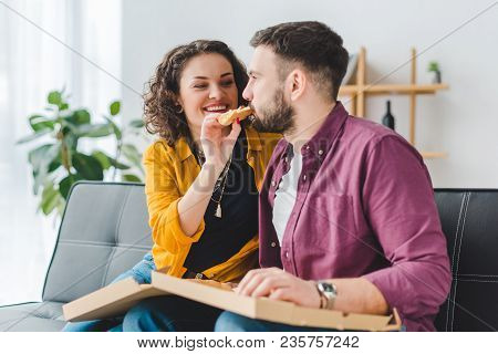 Smiling Woman Feeding Her Boyfriend With Pizza
