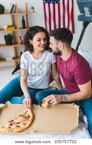 View Of Smiling Couple Sitting And Eating Pizza