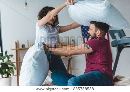Side View Of Young Couple Fighting By Pillows On Bed