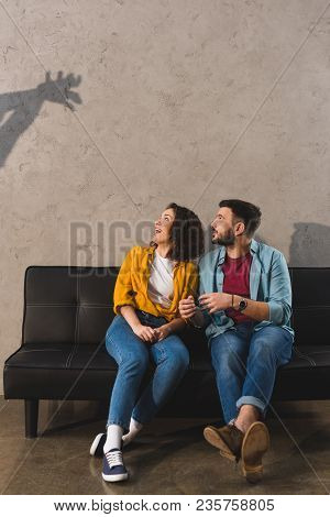 Shadow On Wall And Couple Sitting On Couch