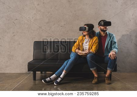 Couple Sitting On Couch And Using Virtual Reality Headset