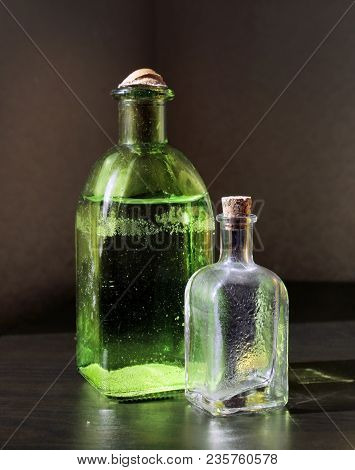 Still Life With Two Small Color Vintage Glass Bottles On The Table Against A Low Key Background. Sha