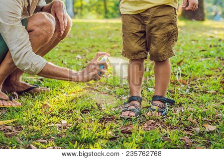 dad and son use mosquito spray.Spraying insect repellent on skin outdoor. poster
