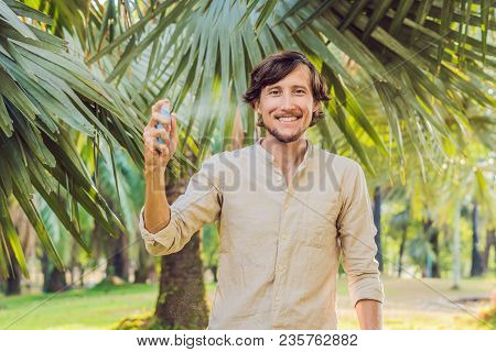 Young Man Spraying Mosquito Insect Repellent In The Forrest, Insect Protection.