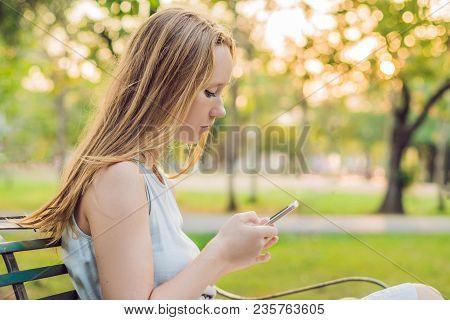 Young Calm Girl Using Her Mobile Phone To Send A Text While Standing In A Park.