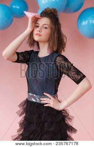 Portrait Of Young Girl In A Birthday Hat Posing At Pink Wall And Blue Balloons, Copy Space.