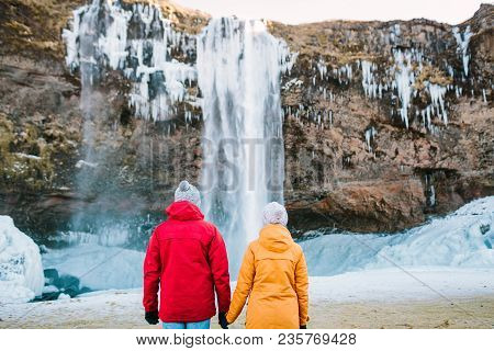 A Young Couple Of Tourists Admire The Waterfall. Rear View