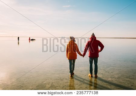 Man In Red Jacket And Woman In Yellow Jacket Walking Together On Ice. Iceland Travelers. Rear View