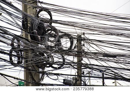 Many Wires Messy With Power Line Cables, Transformers And Phone Lines On Old Electricity Pillar Or U