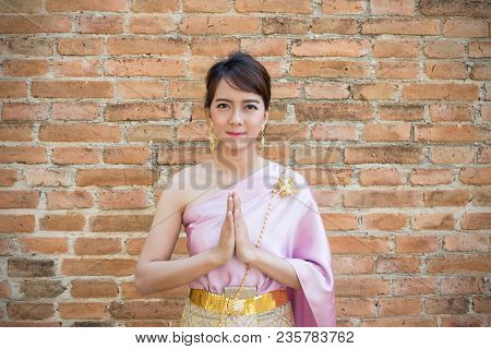 Women Stand Wearing Traditional Cloth Thailand Or Thai Dress With Ancient Walls Background. Welcome