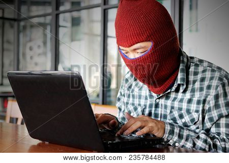 Masked Hacker Wearing A Balaclava Stealing Information Data With Laptop. Internet Crime Concept.