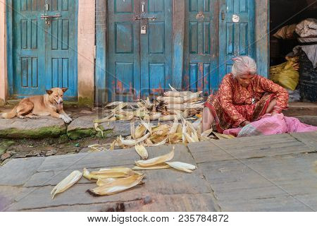 Kathmandu, Nepal - September 22, 2016: Old Nepalese Woman Preparing Corns For Sale On The Street In