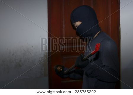Masked Thief With Balaclava Using Crowbar To Breaking Into A House At Night Time. Crime Concept.