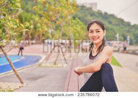 Sports Concept. Beautiful Girl Is Exercising On The Beach With Warm Up. Beautiful Girl Is Happy To E