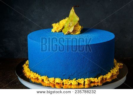 vertical view of piece of delicious blue mousse cake with yellow sponge cake decoration on top and caramel pear inter-layer stands on black mirror background poster