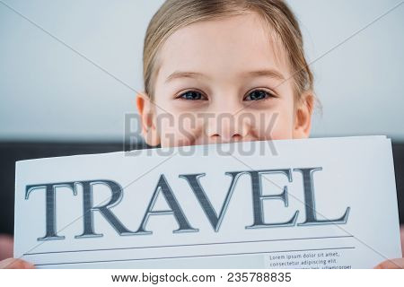 Obscured View Of Cute Child With Travel Newspaper
