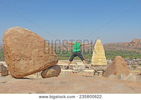 Leap Of A Man. Men Jumping High Back To The Camera Against The Background Of Large Hampi Stones And