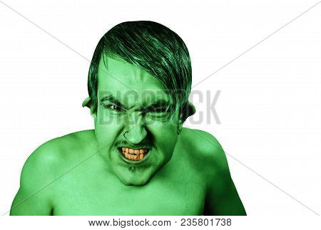 Young Angry Guy In The Image Of A Goblin With Green Skin, Grimaces. Isolated On White Background.