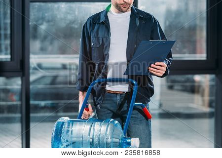 Loader Looking At Cargo Declaration And Holding Delivery Cart With Water Bottles