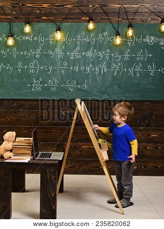 Little Boy Writing On Chalkboard. Side View Kid In Front Of Green Board With Math Equation. Smart Li