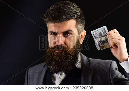 Businessman, Man In Formal Wear With Beard And Mustache On Serious Face Holds Roll Made Out Of Dolla