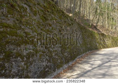 Retaining Stone Wall Next To The Road In The Forest.