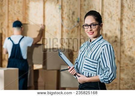 Smiling Businesswoman Holding Cargo Declaration Standing Near Cargo Boxes