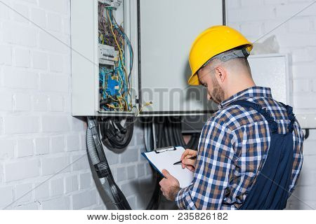 Professional Electrician Inspecting Wires In Electrical Box
