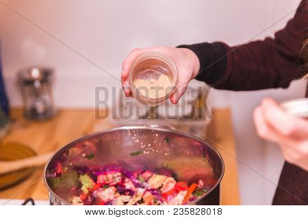 Woman Pouring Seasonings Onto Vegetables In A Stainless Steel Pot.