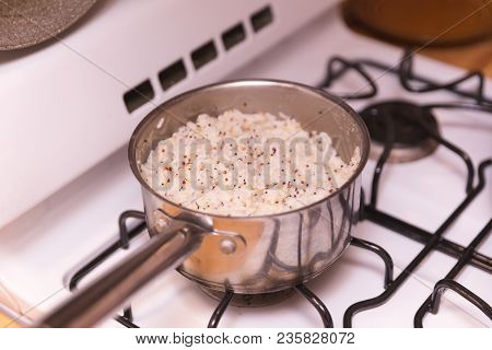 White Rice With Spices Cooking On A Gas Stovetop In A Steel Pot.