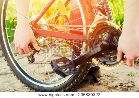 The Guy Repairs The Bicycle. Chain Repair. Cyclist. Unratitude On The Road, Travel, Close-up.