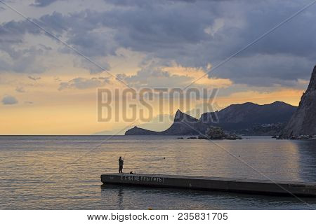 A Lone Fisherman On A Breakwater In Sudak Bay Of Crimea At Evening. Translation Of Phrase: