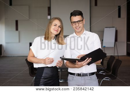 Portrait Of Happy Male And Female Colleagues. Young Caucasian Businessman Wearing Glasses Standing W