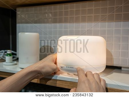 Hand Pressing Timing Button On Electric Aroma Oil Diffuser On Wooden Shelf