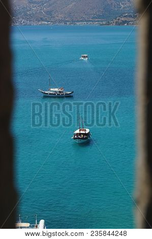 Boats In Aegean Sea Seen Through The Embrasure Of The Spinalonga Fortress