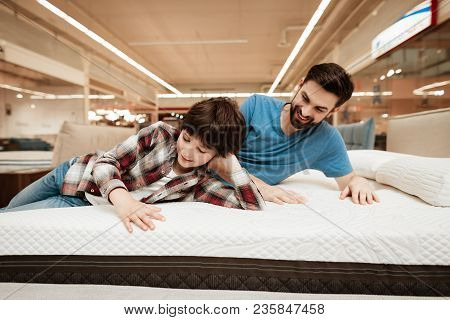 Handsome Bearded Father With Young Son Is Testing Mattress For Softness. Testing Softness Of Mattres