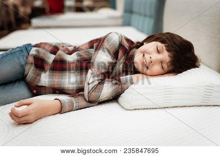 Joyful Boy Enjoying Softness Of Orthopedic Pillow Rejoices In Furniture Store. Joyful Little Boy Lie