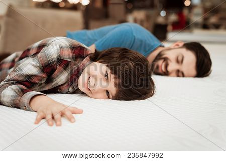 Handsome Bearded Father With Young Son Is Testing Mattress For Softness. Choosing Softness Of Mattre