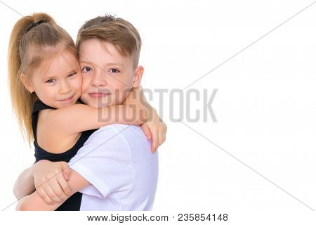 Charming Little Girl Hugging A Tall Boy With Blond Hair. A Romantic Couple Is Happy With The Joint T